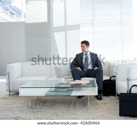 Businessman sitting in a waiting room and using a laptop - stock photo
