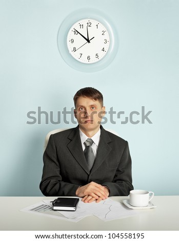 Businessman sitting in an office at the workplace - waiting - stock photo