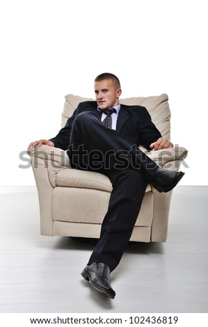 Businessman sitting in armchair with legs crossed isolated - stock photo