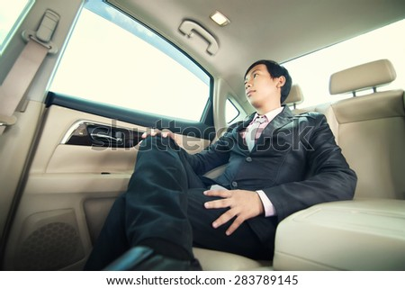 Businessman sitting in car - stock photo