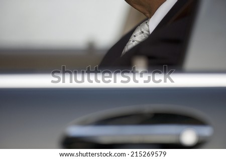 Businessman sitting in car, view through window, side view, close-up (differential focus) - stock photo