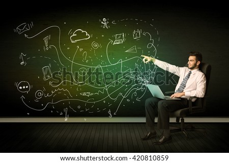 Businessman sitting in chair holding laptop with media icons concept on background