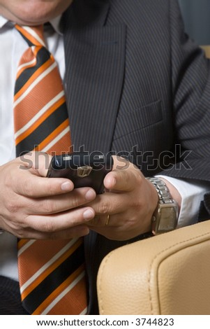 Businessman sitting in chair typing on his mobile phone