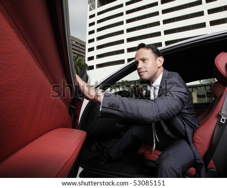Businessman sitting in his car with his hand on the door