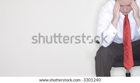 Businessman sitting in his chair with his hands on his hands in frustration and stress - stock photo