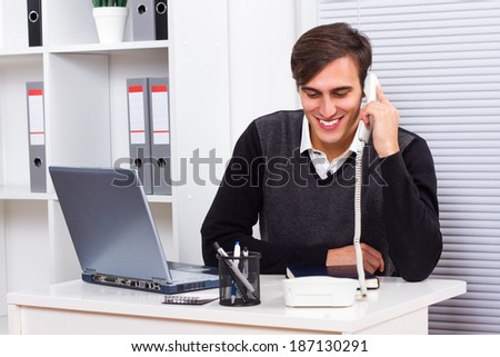 Businessman sitting in his office,working on laptop and talking on the phone,Businessman on the phone - stock photo