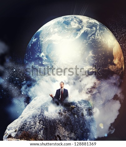 Businessman sitting in lotus flower position against Earth planet background.Elements of this image are furnished by NASA - stock photo