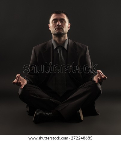Businessman sitting in lotus position against black background. - stock photo