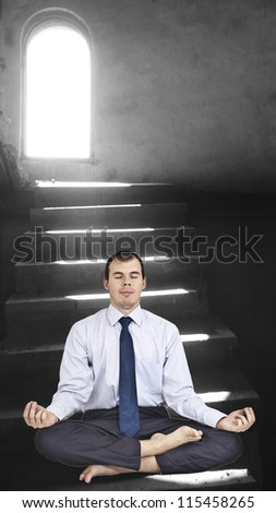 Businessman sitting in lotus position against the light pouring - stock photo