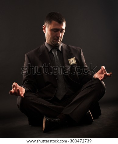 Businessman sitting in lotus position doing yoga and looking at one hundred dollars bill in his pocket.