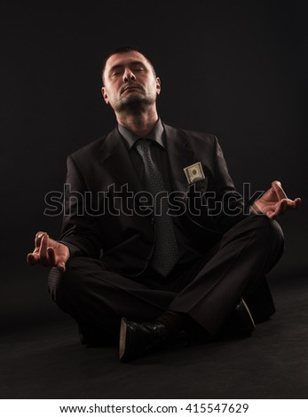 Businessman sitting in lotus position doing yoga with hundred dollars bill in his pocket.