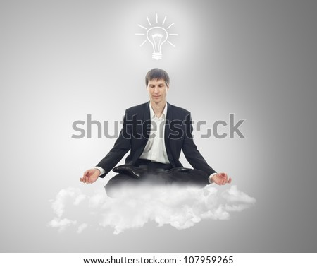Businessman sitting in lotus position on a cloud with a light bulb over your head - stock photo