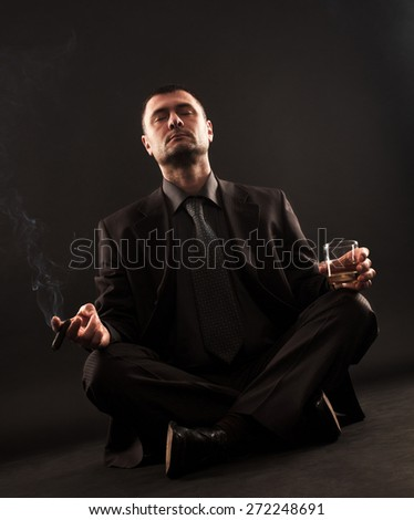 Businessman sitting in lotus position trying to meditate while holding cigar and whiskey in hands.