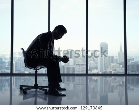 businessman sitting in office and city views in window - stock photo