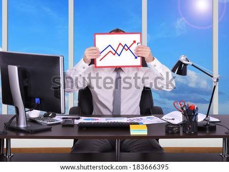 businessman sitting in office and holding clipboard with graph - stock photo