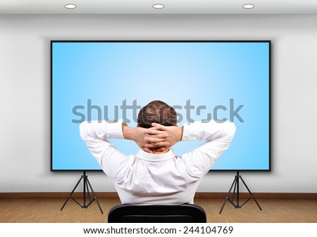 businessman sitting in office and looking to blank  plasma panel - stock photo