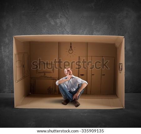 Businessman sitting in office designed in cardboard - stock photo