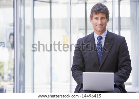Businessman sitting in office lobby using laptop smiling - stock photo