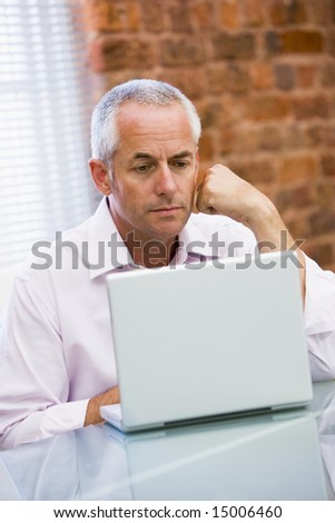 Businessman sitting in office on laptop - stock photo