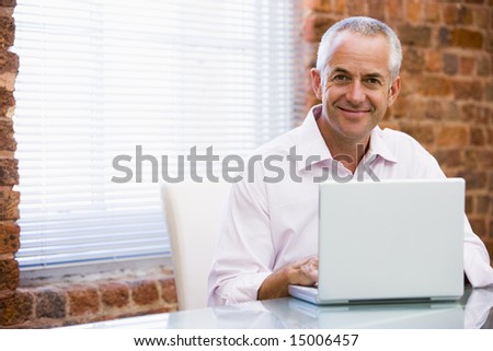 Businessman sitting in office on laptop smiling - stock photo