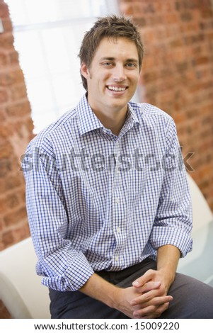 Businessman sitting in office space smiling - stock photo