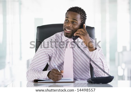 Businessman sitting in office with personal organizer open on telephone - stock photo