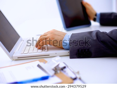 Businessman sitting in office, working with laptop computer - stock photo