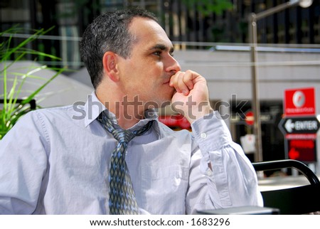 Businessman sitting in outdoor cafe thinking - stock photo