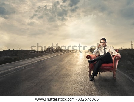 Businessman sitting in red chair in a solitary road in the countryside - stock photo