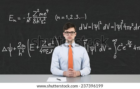 businessman sitting in school and drawing mathematic formula on desk - stock photo