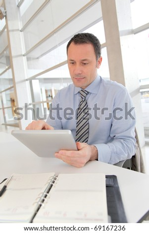 Businessman sitting in the office with electronic tab - stock photo