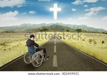 Businessman sitting in the wheelchair on the road with a cross on the sky - stock photo