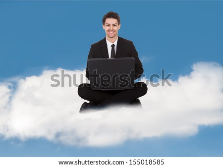 Businessman sitting in yoga pose working on laptop on a cloud - stock photo