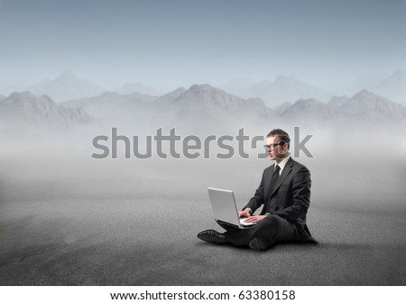 Businessman sitting ina desert and using a laptop