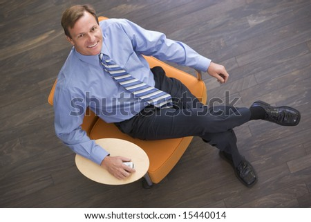 Businessman sitting indoors with cellular phone smiling - stock photo