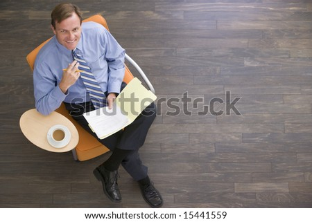 Businessman sitting indoors with coffee and folder smiling - stock photo