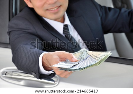 Businessman sitting inside the car giving money - car rental & leasing concept - stock photo