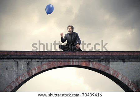 Businessman sitting on a bridge and holding a balloon - stock photo