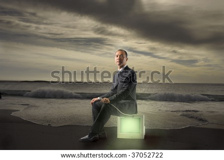 businessman sitting on a bright pc screen on the beach