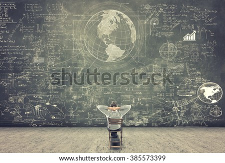 Businessman sitting on a chair and studying math formulas on blackboard - stock photo