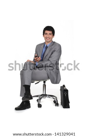 Businessman sitting on a chair and watching TV - stock photo