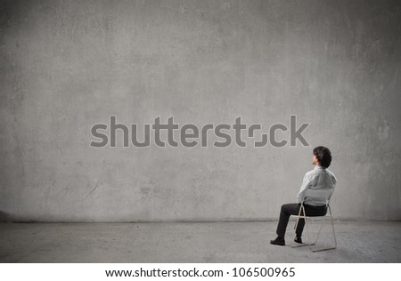 Businessman sitting on a chair in front of a wall - stock photo