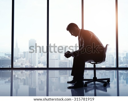 businessman sitting on a chair in office - stock photo
