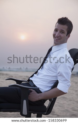 Businessman sitting on a chair in the middle of the desert