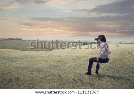 Businessman sitting on a chair on a green meadow and using binoculars - stock photo