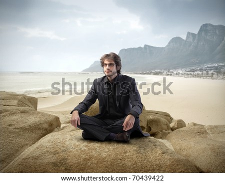 Businessman sitting on a cliff at the seaside - stock photo