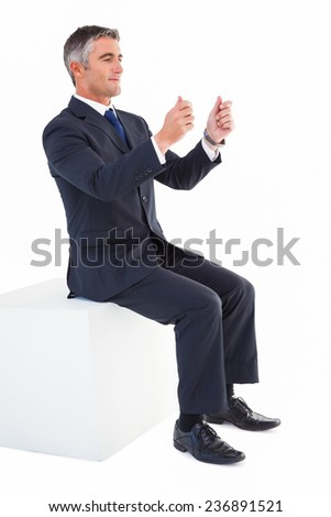 Businessman sitting on a cube with arms out on white background