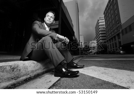Businessman sitting on a curb in the city