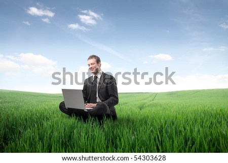 Businessman sitting on a green meadow and using a laptop