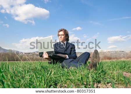Businessman sitting on a green meadow and using a laptop - stock photo